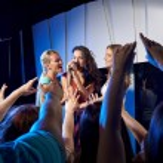 Happy young women singing karaoke in night club — Stock Photo #65169717