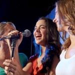 Happy young women singing karaoke in night club — Stock Photo #65169757