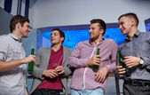 Group of male friends with beer in nightclub — Stock Photo