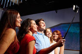 Friends with smartphone taking selfie in club — Stock Photo