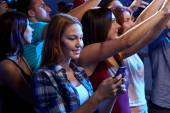 Woman with smartphone texting message at concert — Stock Photo
