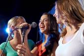 Happy young women singing karaoke in night club — Stock Photo