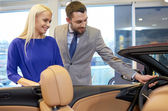Happy couple buying car in auto show or salon — Stock Photo