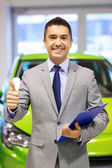 Man showing thumbs up at auto show or car salon — Stock Photo