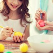 Close up of little girl and mother coloring eggs — Stock Photo #65368171