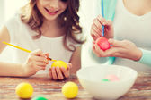 Close up of little girl and mother coloring eggs — Foto Stock