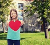 Smiling little girl giving red heart — Stock Photo