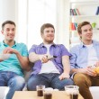Happy male friends watching tv at home — Stock Photo #65371545