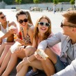 Group of smiling friends sitting on city square — Stock Photo #65375541
