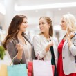 Happy young women with shopping bags in mall — Stock Photo #65376109
