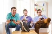 Smiling friends playing video games at home — Stock Photo