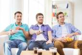 Happy male friends watching tv at home — Stock Photo