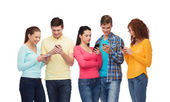 Group of smiling teenagers with smartphones — Stock Photo