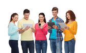 Group of teenagers with smartphones and tablet pc — Stock Photo
