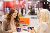 Smiling young women drinking coffee in mall — Stock Photo
