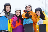 Happy friends in helmets with snowboards — Stock Photo