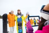 Happy friends with snowboards and tablet pc — Stockfoto