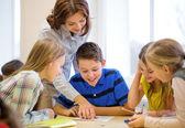Group of school kids writing test in classroom — Foto de Stock