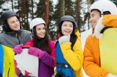 Happy friends in helmets with snowboards talking — Stock Photo