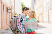 Smiling couple with map and backpack in city — Stock Photo