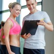 Smiling young woman with personal trainer in gym — Stock Photo #65464115