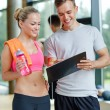 Smiling young woman with personal trainer in gym — Stock Photo #65464119