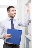 Gut aussehend kaufmann-Kommissionierung-Ordner im Büro — Stockfoto