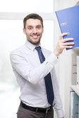 Handsome businessman picking folder at office — Stock Photo