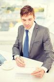 Homme d'affaires avec ordinateur portable et documents — Photo