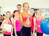 Smiling sporty woman with water bottle and towel — Stock fotografie