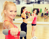 Smiling beautiful sporty woman with dumbbell — Stock Photo
