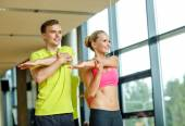 Smiling man and woman exercising in gym — Stock Photo