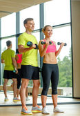 Smiling man and woman with dumbbells in gym — Stock Photo