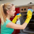 Happy woman cleaning cooker at home kitchen — Stock Photo #65658491
