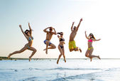 Smiling friends in sunglasses on summer beach — Stock Photo