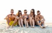Friends with smartphones on beach — Stock Photo