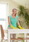 Happy woman cleaning table at home kitchen — Stock Photo