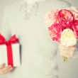 Man holding bouquet of flowers and gift box — Stock Photo #65679805