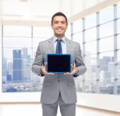 Happy businessman in suit showing tablet pc screen — Stock Photo
