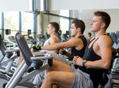 Men working out on exercise bike in gym — Stock Photo