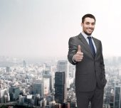 Handsome buisnessman showing thumbs up — Stock Photo