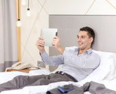 Happy businesswoman with tablet pc in hotel room — Stock Photo