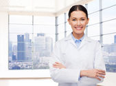 Smiling young female doctor in white coat — Stock Photo