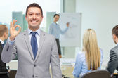 Happy businessman in suit showing ok hand sign — Stock Photo