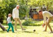 Happy family playing football outdoors — Stock fotografie