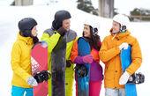 Happy friends in helmets with snowboards talking — Stockfoto