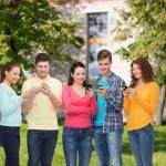 Skupina teenagerů usmívající se smartphony — Stock fotografie #66075261