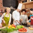 Happy friends and chef cook cooking in kitchen — Stock Photo #66076883