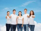 Smiling teenagers in t-shirts showing thumbs up — Stock Photo