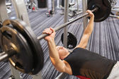 Young man flexing muscles with barbell in gym — Stockfoto